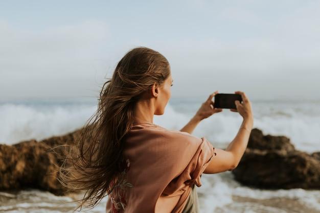 Woman taking photos with her phone on the beach