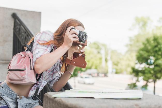 Donna che cattura maschera sulle attrazioni della città