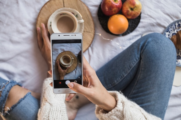 Woman taking picture of coffee with smartphone