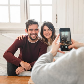 Woman taking picture of couple at home