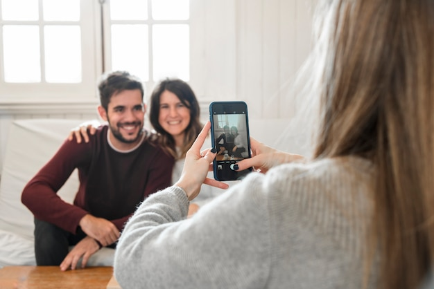 Woman taking picture of couple with phone