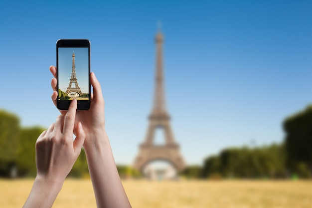 Woman taking a picture of of eiffel tower, view from champ de mars in the morning with a blue sky in a background