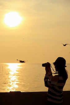 Woman taking picture of flying seagulls during the sunrise over the gulf of thailand