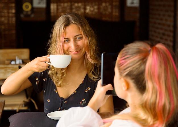 Donna che cattura maschera della sua amica mentre beve il caffè