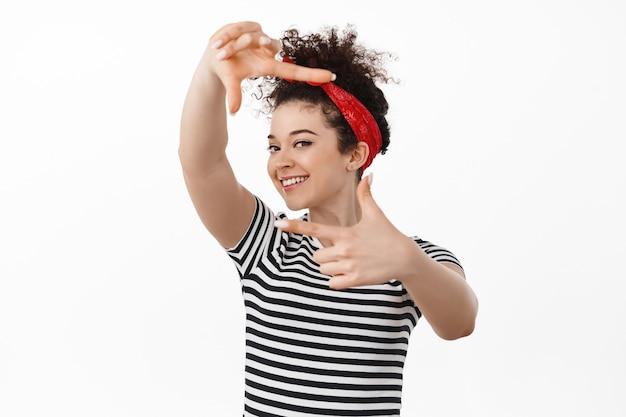 Donna che scatta foto, guarda attraverso il gesto della fotocamera con le cornici delle mani, salva il momento nei ricordi, fa un piano creativo, sta sopra il bianco