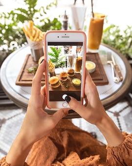 レストランでハンバーガーメニューの写真を撮る女性