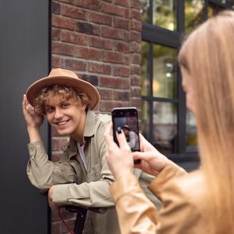 Женщина фотографирует своего парня с электросамокатом