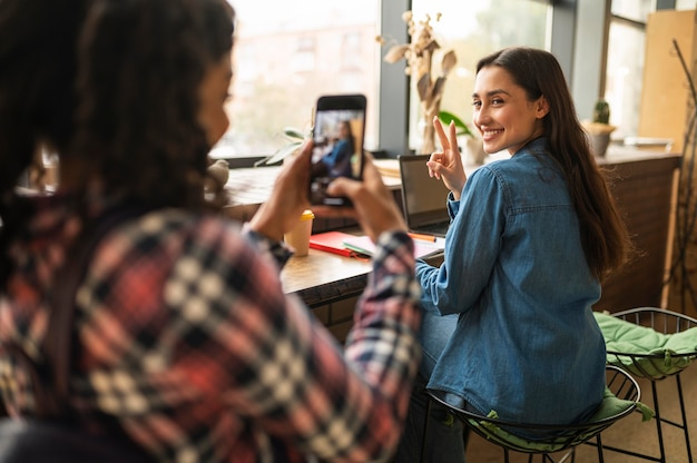 Женщина фотографирует своего друга в кафе
