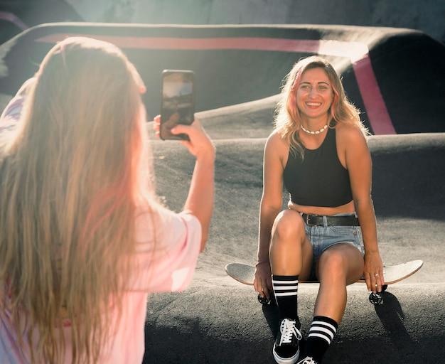 スケートリングで彼女の友人の写真を撮る女性
