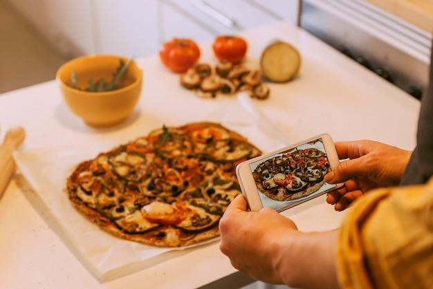おいしいピザに写真を撮る女性。自家製のコンセプト。