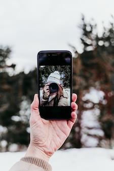 携帯電話に写真を撮る女性、自分撮り。技術とライフスタイル。雪山