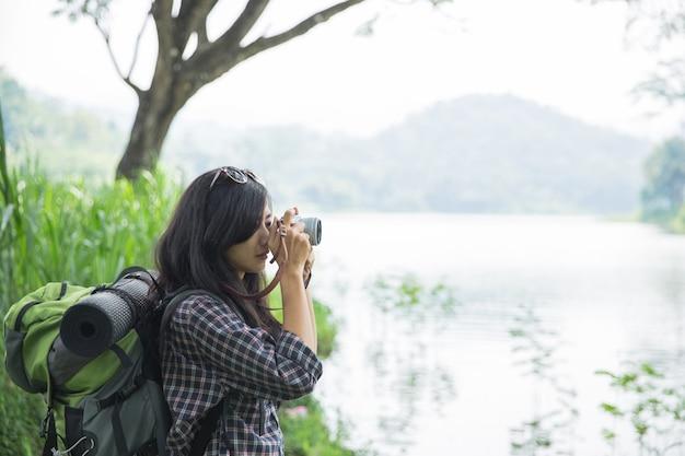 Женщина фотографируя с камерой пока пеший туризм