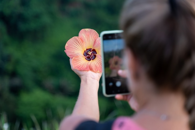 Woman taking a picture with her mobile phone of a flower she is holding in her hand