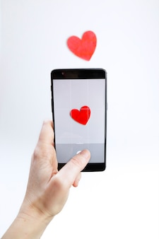 Woman taking a picture with her smartphone of a red wooden heart