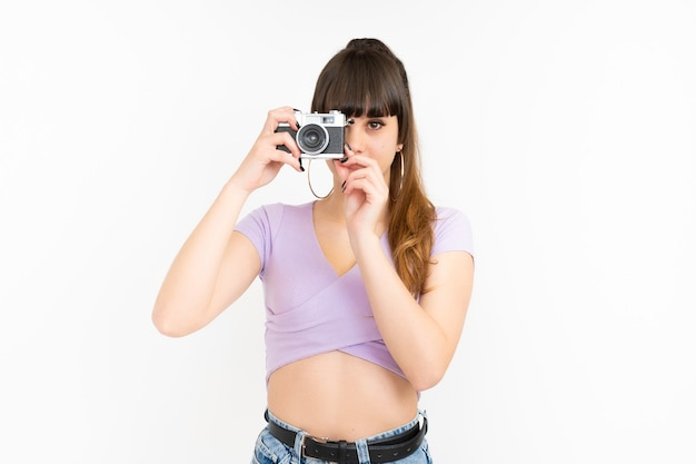 Woman taking picture with photo camera on white