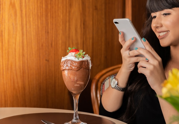 Woman taking pictures of delicious ice cream white blends strawberry with a smart phone.