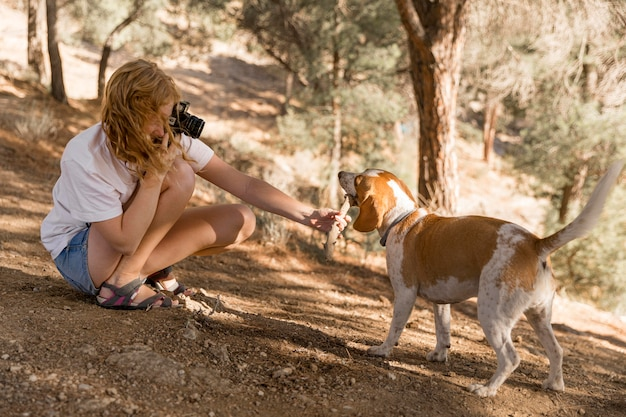 Woman taking pictures of her dog side view