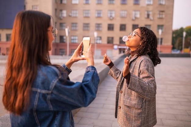 Donna che cattura immagini della sua amica che soffia bolle all'aperto