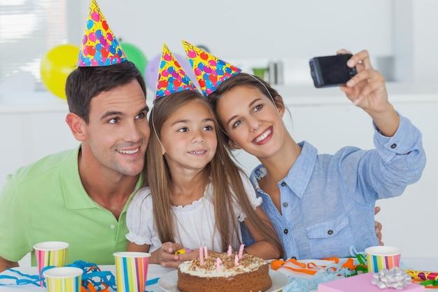 Женщина фотографирует свою семью во время празднования дня рождения