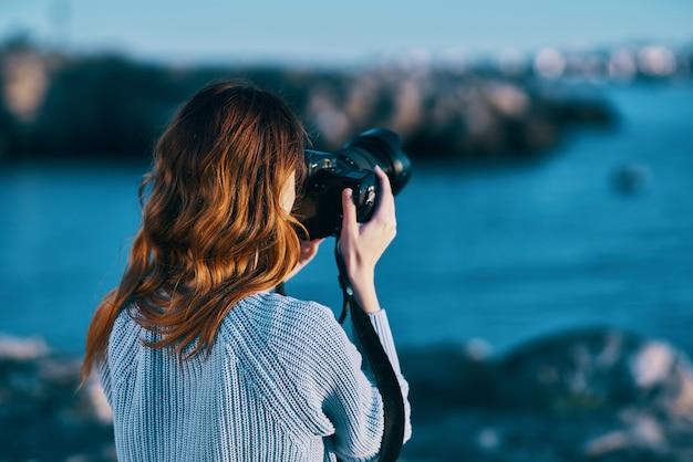 山の背面図でカメラの海で写真を撮る女性