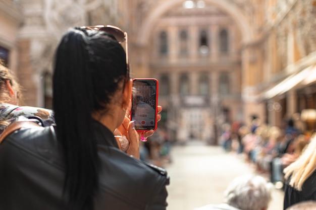 Женщина фотографирует с помощью смартфона или снимает видео моделей на подиуме в городе