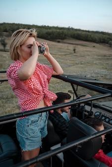 자동차로 여행하는 동안 사진을 찍는 여자