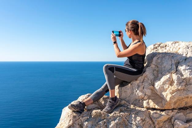 カルペのペニョンデイファクから自然の中で、スマートフォンで風景に写真を撮る女性