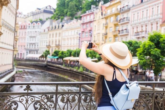 스마트 폰으로 사진을 찍는 여자. 야외에서 카메라와 모자에 세련 된 여름 여행자 여자