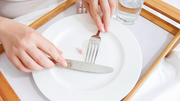 Woman taking pill with knife and fork from empty dish. concept of dieting, weight loss and medicine.