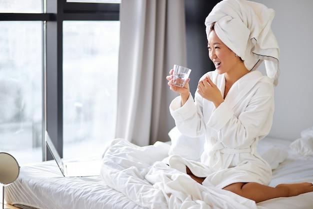 Женщина принимает таблетки и стакан воды для лечения утром. милая женщина пьет витамины для профилактики болезней. концепция благополучия и здоровья