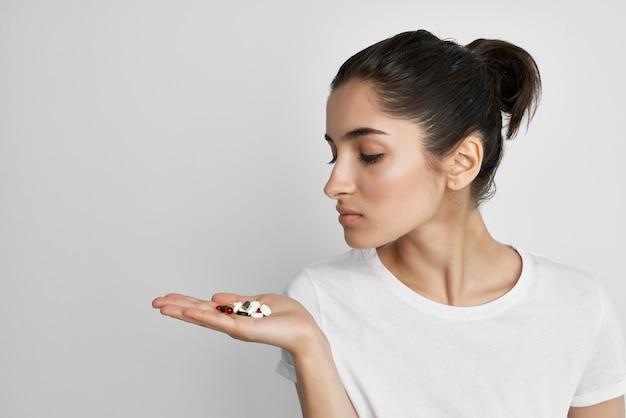 カプセルで錠剤を服用している女性は、健康的なライフスタイル療法を形成します。高品質の写真