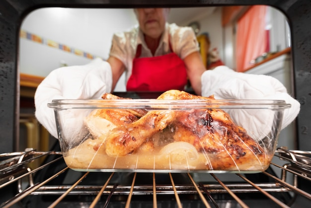 Woman taking roasted chicken from the oven. cooking in the oven.