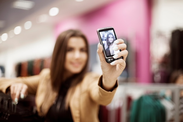 Woman taking self portrait photo in shopping mall