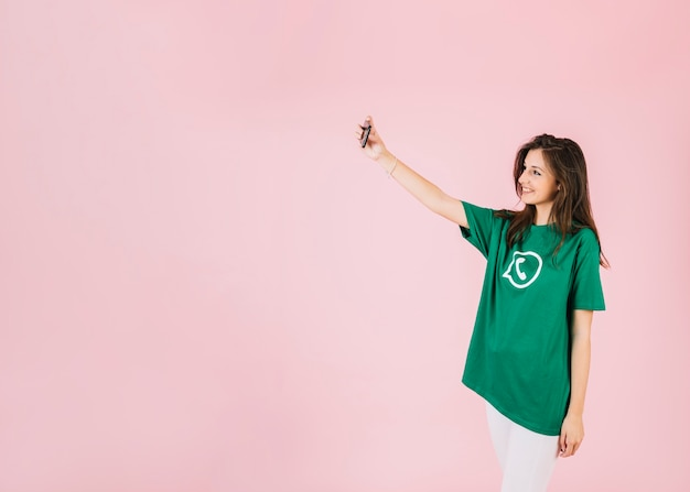 Woman taking selfie on cellphone wearing whatsapp icon t-shirt