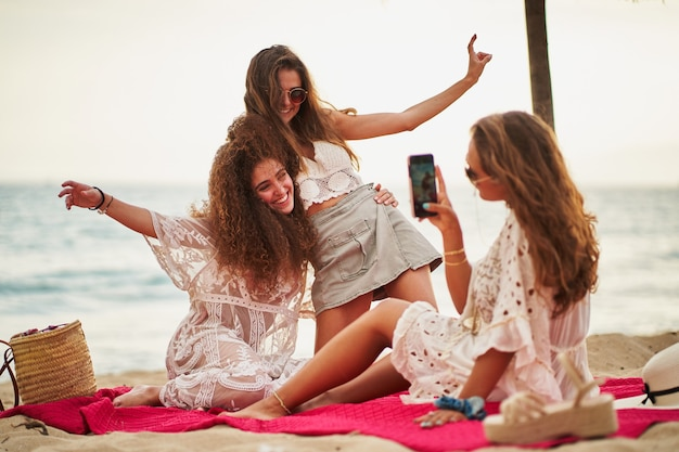 Woman taking selfie to her friends on a red towel at beach