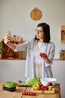 셀카를 찍거나 요리에 대한 비디오 강의를하는 여성
