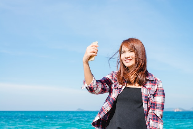 Woman taking selfie using smartphone at sea travel lifestyle.