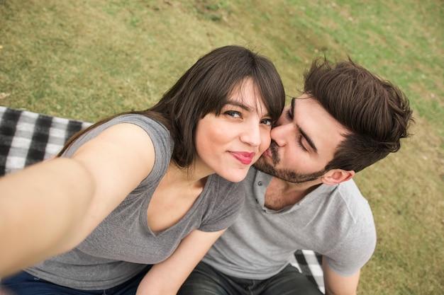 Woman taking selfie while her boyfriend kissing