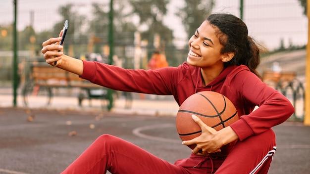 Donna che cattura un selfie con un pallone da basket