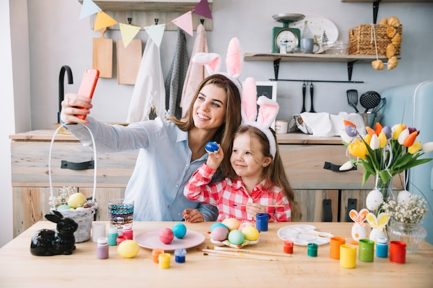 Woman taking selfie with daughter near easter eggs