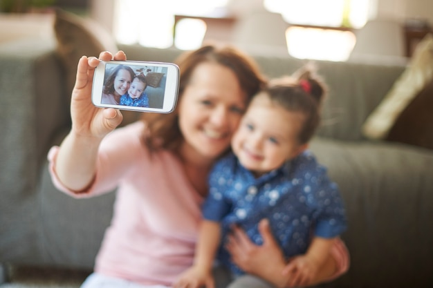 Woman taking selfie with her daughter