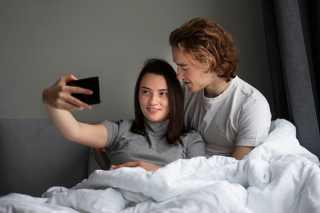 Woman taking selfie with man while in bed