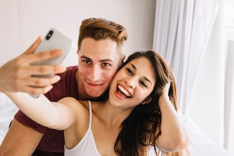 Woman taking selfie with man