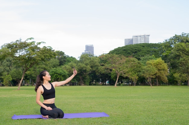 Woman taking selfie with mobile phone while sitting on yoga mat