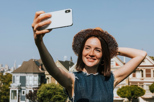 Woman taking a selfie with the painted ladies of san francisco, usa