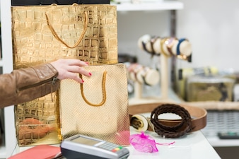 Woman taking shopping bag from counter
