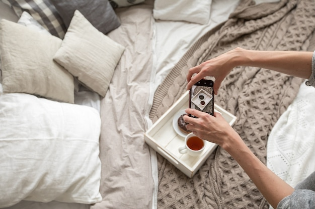 Woman taking shot of tray with food on bed