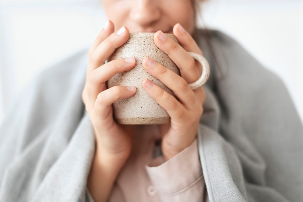 Woman taking a sip of tea from the mug during winter
