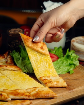 Woman taking a slice of turkish pide bread with melted cheese.