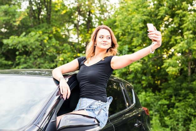 Woman taking smartphone selfie photo on car summer travel vacation. pretty girl leaning out car window